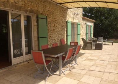 Vue sur la terrasse avec sa table pour 8 personnes et le petit salon extérieur.