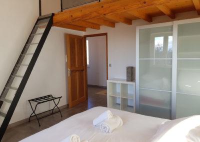 Vue d'ensemble de la chambre N°4 avec l'escalier qui monte à la mezzanine.
