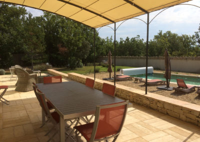 La terrasse et la piscine vue de la baie vitrée.
