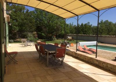 Vue sur la terrasse, le terrain et la piscine.