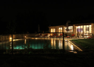 Vue de nuit sur l'ensemble piscine et Pool House.