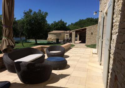 Vue du coin salon extérieur avec la piscine et le Pool House au fond.