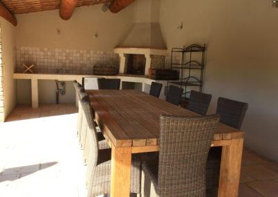 Le Pool House avec sa table, son barbecue et sa cuisine d'été.